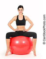 Brunette woman excercising with a pilates ball - studio shot...