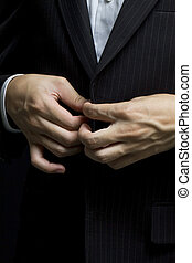 Business man tidy up his suit's button, makes a neat image.