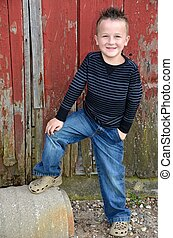 young lad by old barn