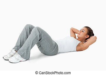 Young female doing sit ups against a white background