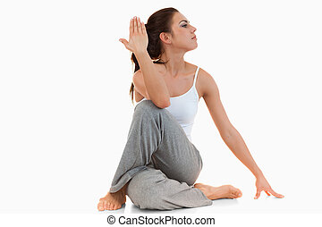 Portrait of a woman in the Ardha Matsyendrasana position...