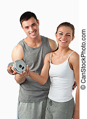 Portrait of a man helping a smiling woman to work out