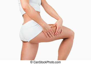 Fit woman touching her thigh against a white background