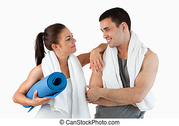 Healthy couple going to practice yoga against a white...