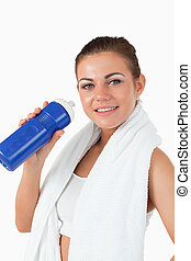 Smiling woman with her bottle after workout