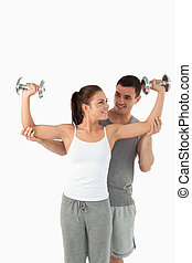 Portrait of a young man helping a smiling woman to work out