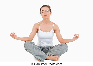 Woman in the Sukhasana position against a white background