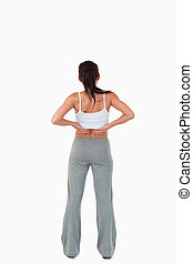 Back view of woman with hands on her hip against a white...