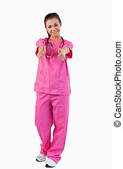 Portrait of a brunette doctor with thumbs up against a white...