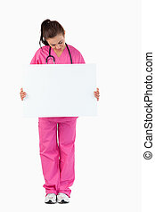 Portrait of a brunette doctor holding a blank panel against...