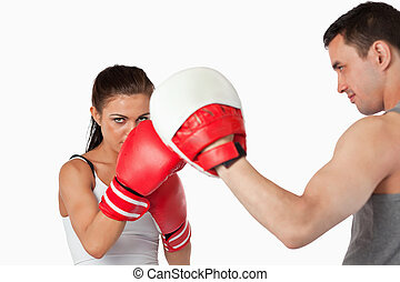 Female boxer with strong fighting spirit against a white...