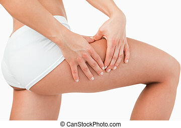 Woman touching her thigh against a white background