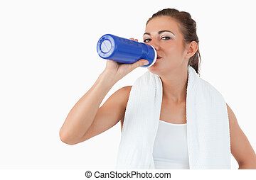 Atletic female taking a sip of water after training