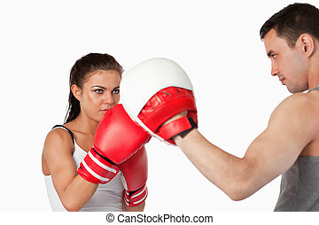 Female boxer focused on her training against a white...