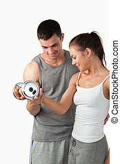 Portrait of a handsome man helping a woman to work out