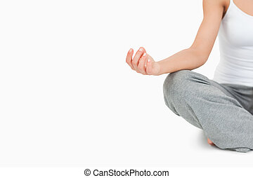 Fit woman in the Sukhasana position against a white...