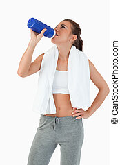 Young female taking a sip out of her bottle after workout