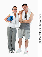 Portrait of a couple going to practice yoga against a white...