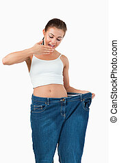 Portrait of a suprised woman wearing too large jeans against...
