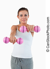 Portrait of a smiling woman working out with dumbbells...