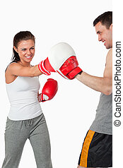Aggressive female boxer striking her target against a white...