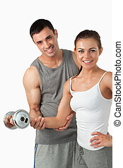 Portrait of a smiling man helping a woman to work out...