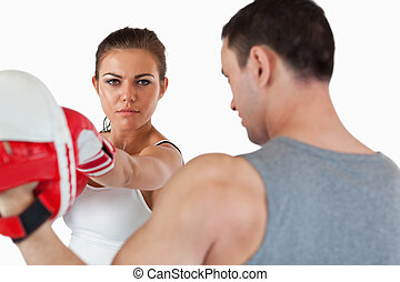 Confident looking female with her martial arts trainer...