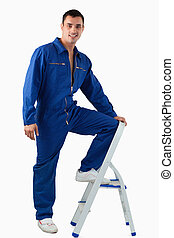 Portrait of a handsome mechanic climbing on a stool