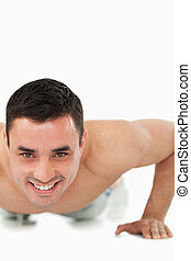 Smiling young male doing push ups
