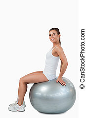 Portrait of a smiling woman working out with a ball against...