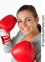 Portrait of a smiling woman with boxing gloves against a...