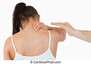 Back view of female having pain in her neck against a white...