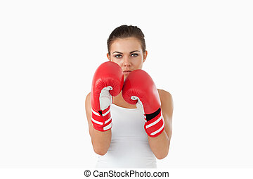 Female boxer in defensive stance against a white background