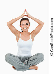 Portrait of a woman in a meditation position against a white...
