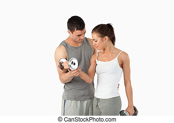 Man helping a young woman to work out