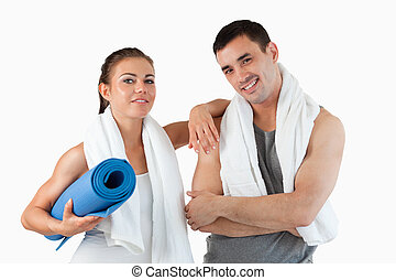 Fit couple going to practice yoga against a white background