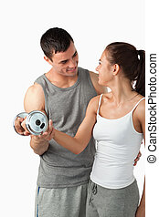 Portrait of a man helping a young woman to work out