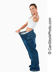 Portrait of a fit woman wearing too large pants with the...
