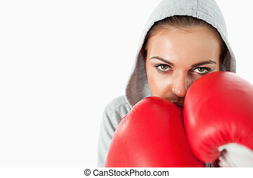 Female boxer with hoodie on in defensive position against a...