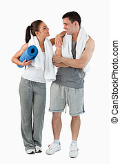 Portrait of a happy couple going to practice yoga against a...