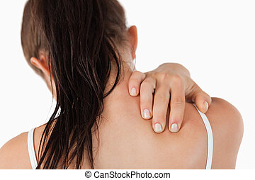 Back view of young woman with neck pain against a white...