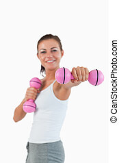 Portrait of a happy woman working out with dumbbells
