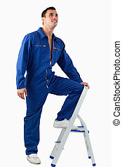 Portrait of a mechanic climbing on a stool against a white...