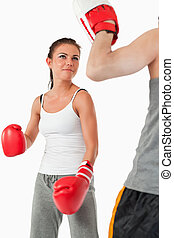 Young female in martial arts training against a white...