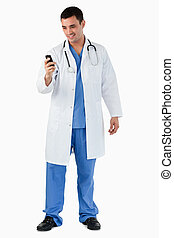 Portrait of a doctor dialing on his mobile phone against a...