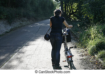 Woman walking uphill with bicycle - Woman walking on an...