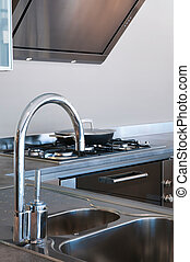 Water tap and sink in a modern kitchen interior