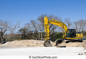 BackHoe - Bright yellow tract backhoe on construction site...