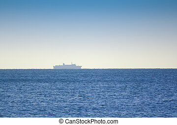 Transport ship on the horizon on a sunny day