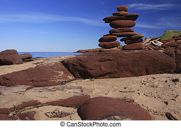 Inukshuk made of Red rocks on a Prince Edward Island Beach...